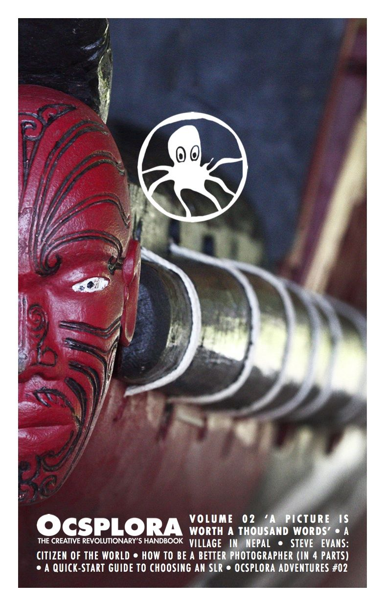 The cover of OCSPLORA Volume Two, carved wooden head at the front of a Maori longboat, red face with black tattoo lines and white eyes and black pupils