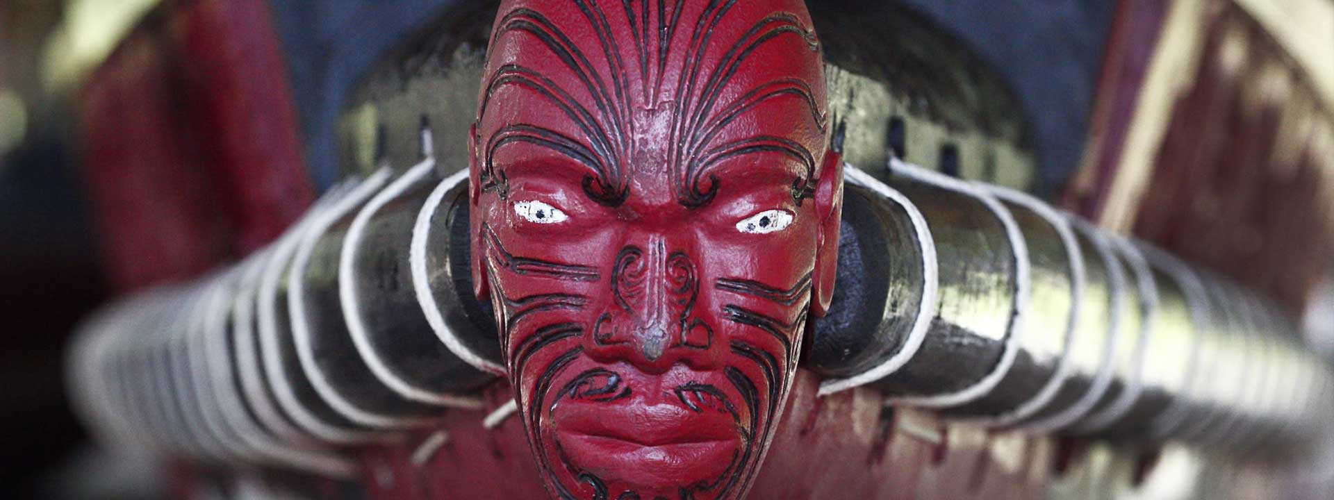 Front of a Maori longboat, carved face painted red with black tattoos. Original photo by Steve Evans.